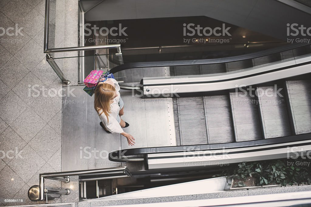 Above view of a woman going on an escalator. stock photo