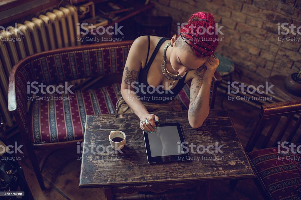 Above view of a woman using electronic organizer at cafe. stock photo