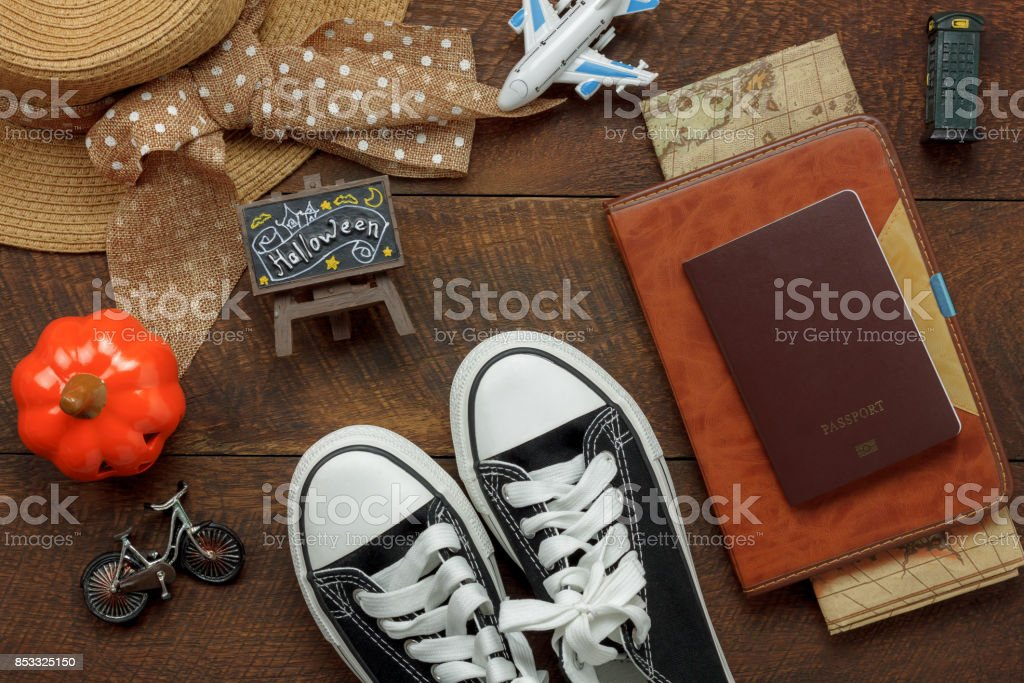 Above view of accessory Happy Halloween with items to travel background concept.Mix several object on the modern rustic brown wooden at home office desk.Equipment for traveler or teenage and adult. stock photo