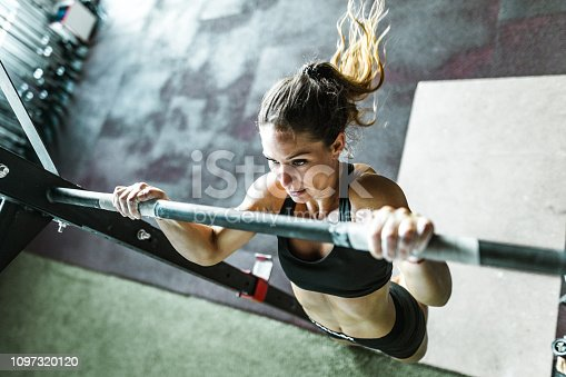 High angle view of determined female athlete exercising chin-ups during cross training in a health club.