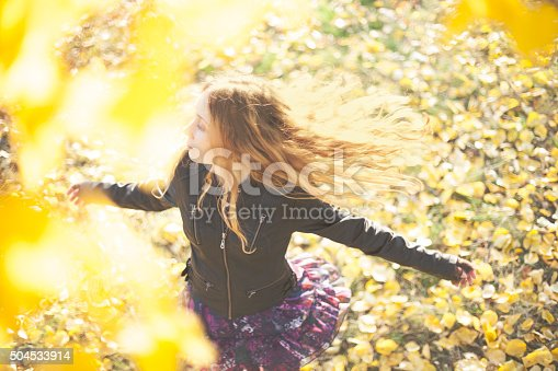 High angle view of running girl wearing leather jacket.  She is dancing and swirling around.