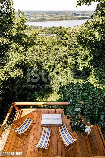 High angle view of balcony with deck chairs and table among greenery.