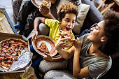 High angle view of happy African American girl being fed by her mother with pizza at home.
