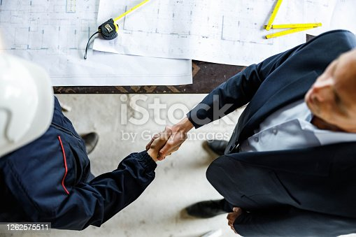 961745166 istock photo Above view of building contractor and worker came to an agreement at construction site. 1262575511