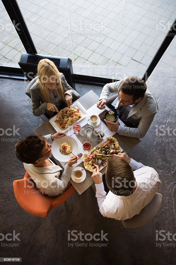 Directly above view of four business colleagues eating in restaurant...