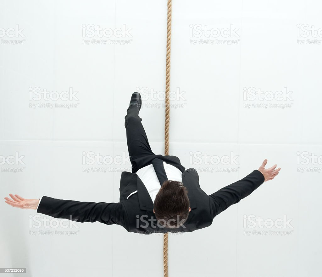 Above view of businessman walking on tightrope stock photo
