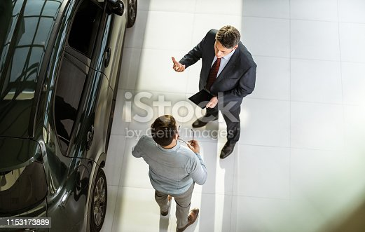 High angle view of a salesperson using touchpad while talking to his male customer in a car showroom. Copy space.