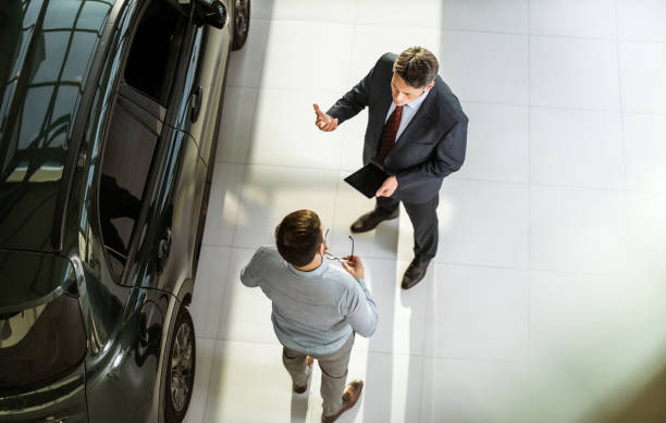Above view of car salesperson talking to his customer in a showroom. High angle view of a salesperson using touchpad while talking to his male customer in a car showroom. Copy space. car salesperson stock pictures, royalty-free photos & images