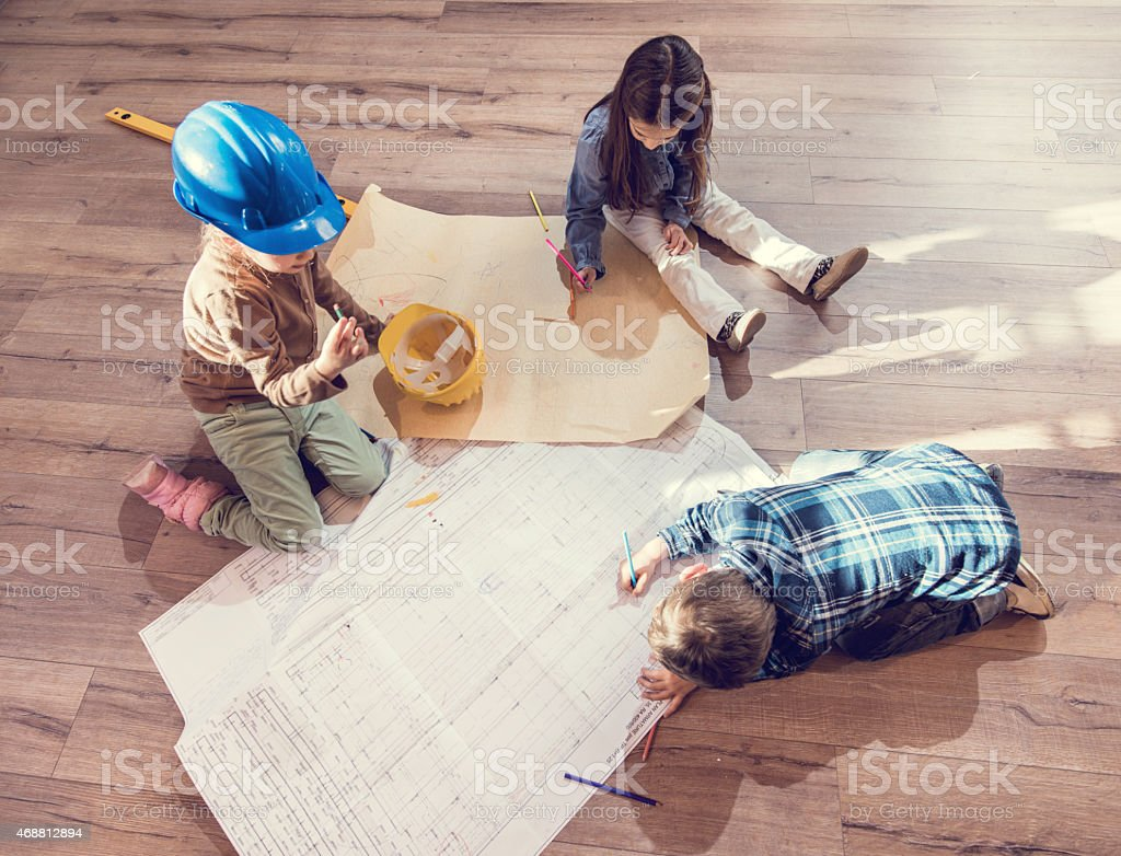 above view of children architects working on blue prints stock