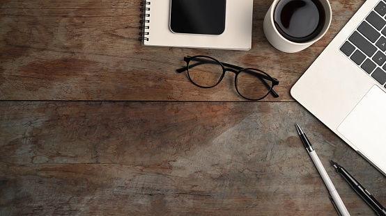 Above view of computer laptop, coffee cup, smart phone, eye glasses and notebook on wooden table.