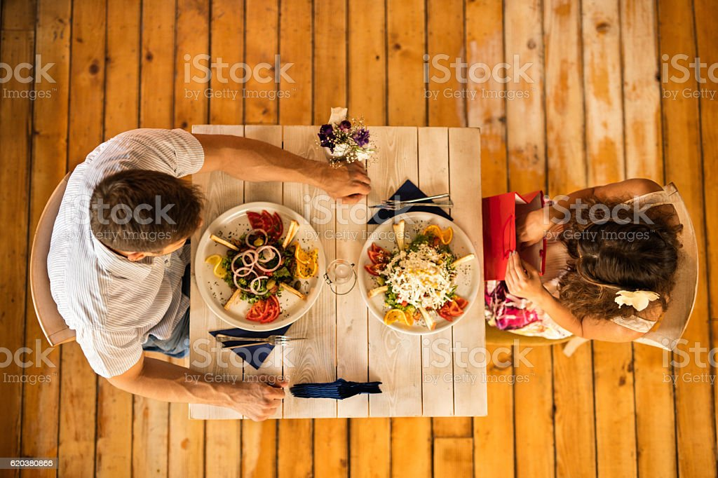 High angle view of woman looking at surprise shopping bag she has...
