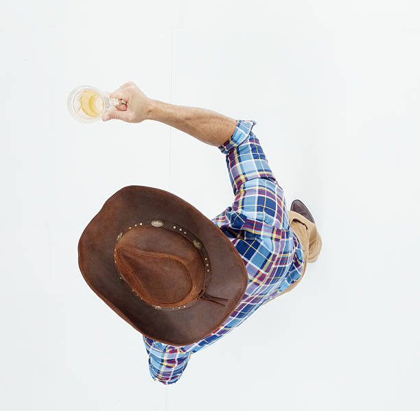 Above view of cowboy holding beer glass stock photo