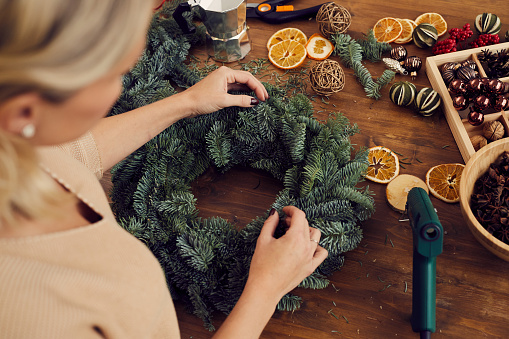 Above view of craftswoman standing at wooden table full of decorations and creating Christmas wreath in workshop
