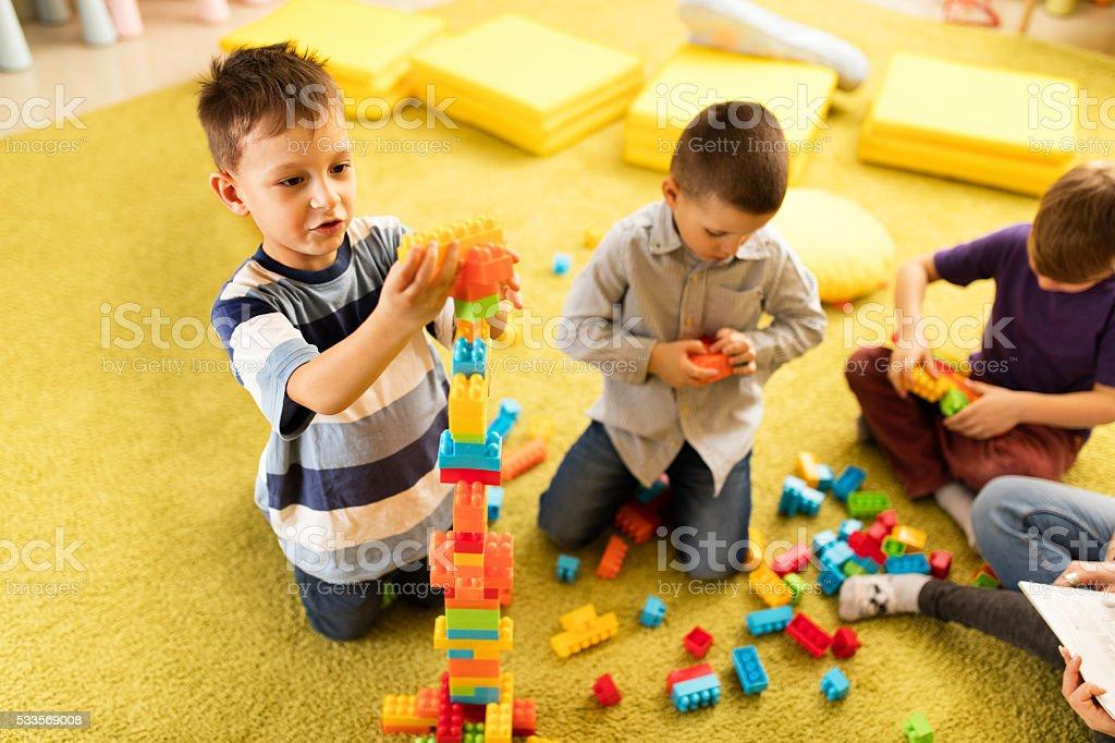 3bd40d8ee5 Vista dall'alto di creativo piccolo ragazzo che gioca con giocattoli  isolati. foto stock