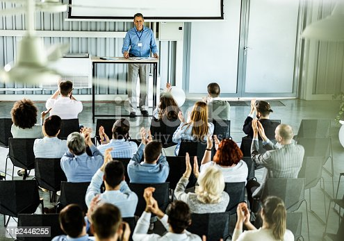 894290604 istock photo Above view of crowd of entrepreneurs applauding on training class in a board room. 1182446255