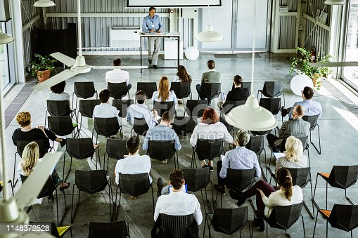 istock Above view of crowd of entrepreneurs having training class in a board room. 1148372528
