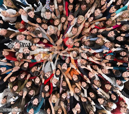 High angle view of large group of happy people joining hands in unity and looking at camera.