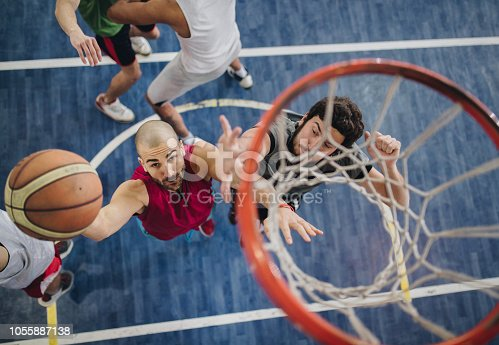 High angle view of a basketball players playing a match on a court, while one of them is about to score.