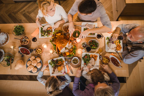 above view of extended family talking at thanksgiving dinner. - pranzo di natale foto e immagini stock
