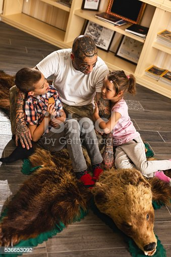 High angle view of young father talking with his son and daughter while sitting on bearskin rug.
