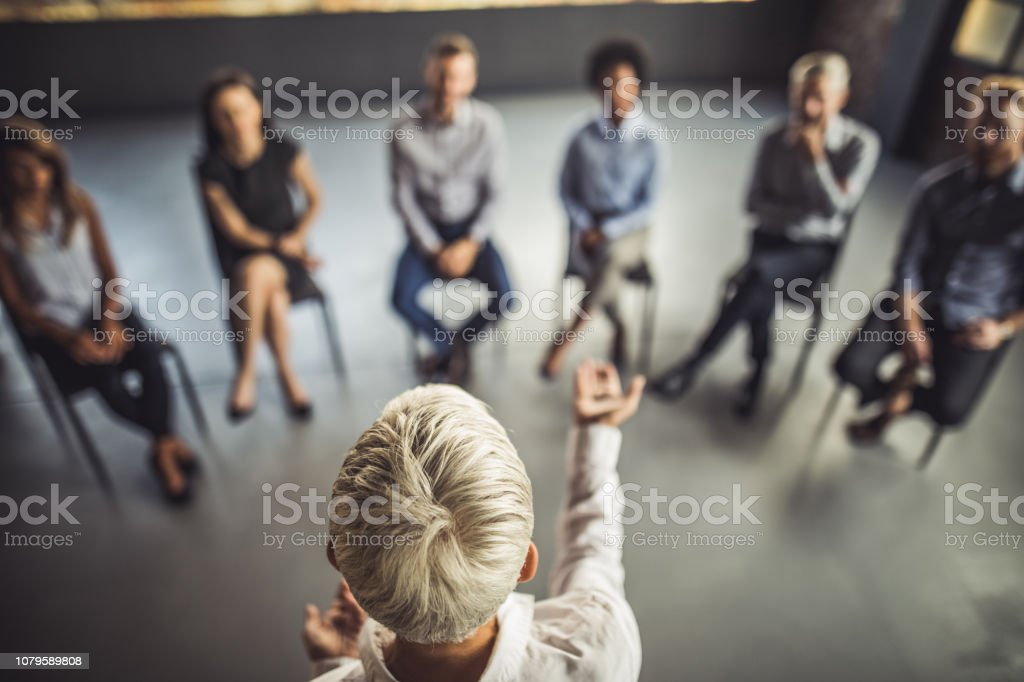 Above view of female instructor leading a business group therapy. - Zbiór zdjęć royalty-free (Biuro)