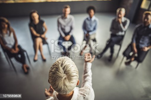 High angle view of businesswoman talking to large group of her colleagues on a group therapy in the office.