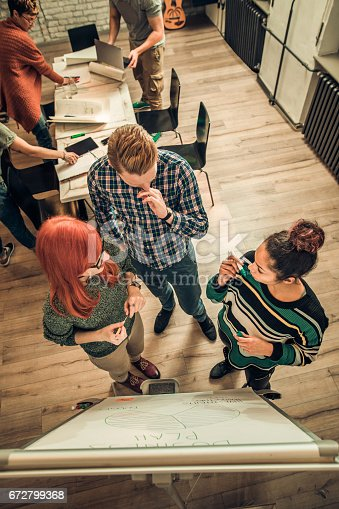 497812268 istock photo Above view of freelance team talking about business plan in the office. 672799368
