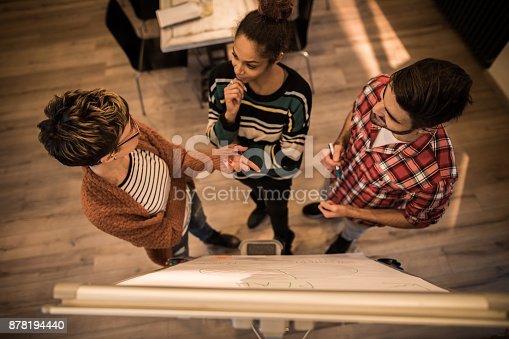 497812268 istock photo Above view of freelance team talking about business plan in the office. 878194440