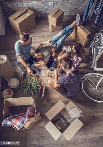 istock Above view of friends  relaxing and using wireless technology after relocating into a new apartment. 820826672