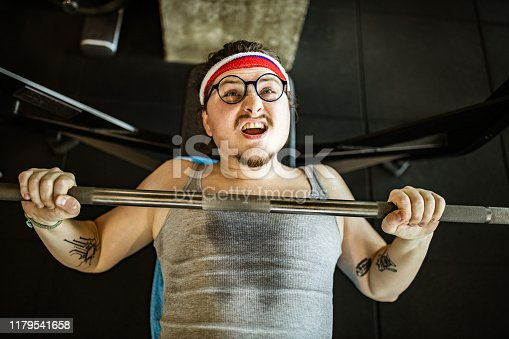 High angle view of nerdy male athlete making an effort while exercising on a bench press in a gym.