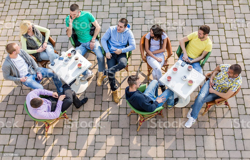 Above view of group of young people relaxing in cafe. stock photo