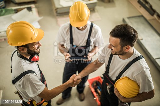 961745166istockphoto Above view of happy construction workers shaking hands while working on home renovation process. 1054944326
