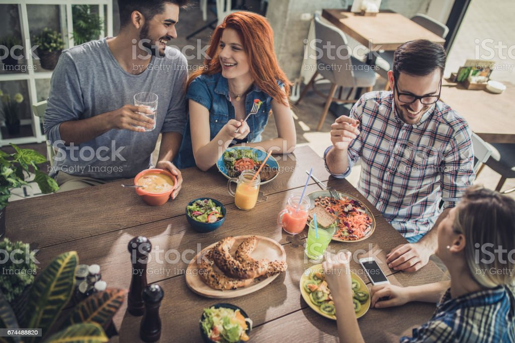 High angle view of happy friends sitting on a lunch in a cafe and...