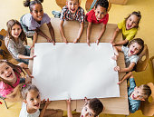 High angle view of large group of happy students shouting and looking at camera while holding blank paper in the classroom. Copy space.