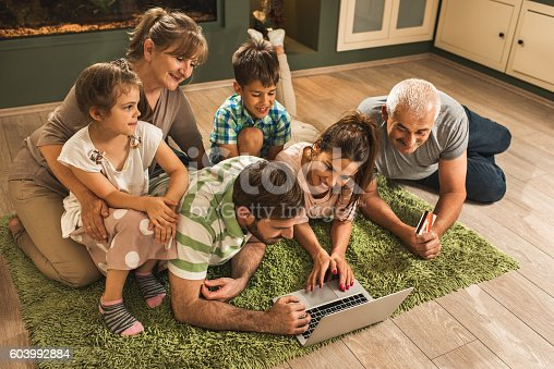 High angle view of smiling multi-generation family relaxing on carpet at home and shopping online.