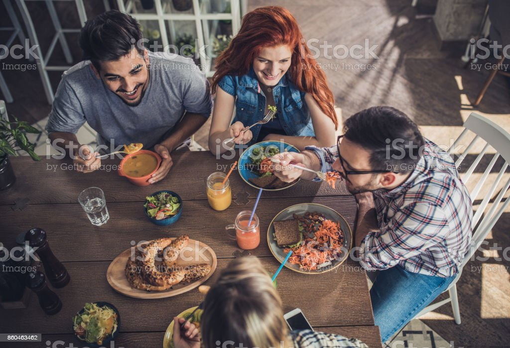 high angle view of young happy people having a lunch in a restaurant...