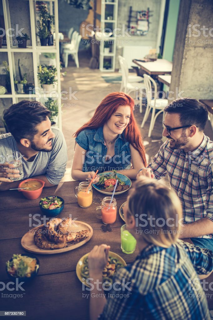 Above view of happy friends having lunch together and communicating. stock photo