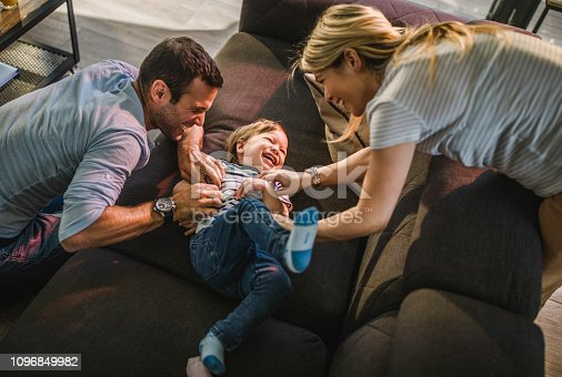 1159543952istockphoto Above view of happy parents tickling their joyful son on sofa at home. 1096849982