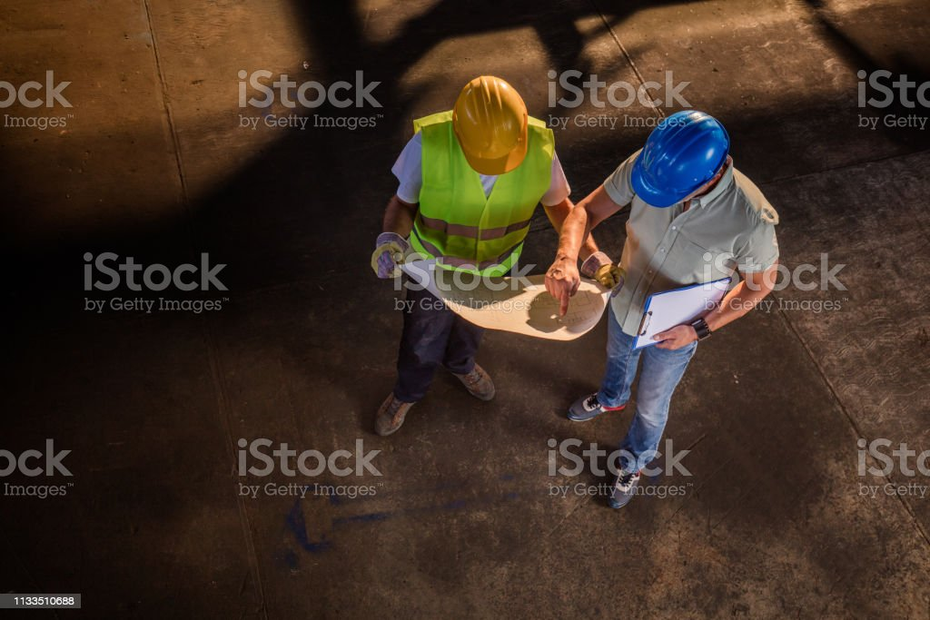High angle view of manager and worker analyzing blueprints in a...