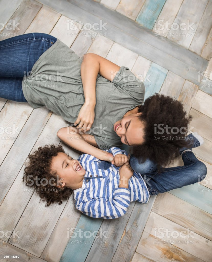 Above view of joyful African American mother and son having fun on wooden floor. High angle view of cheerful black mother having fun with her small son on wooden floor at home. Adult Stock Photo
