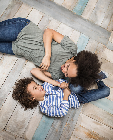 Above View Of Joyful African American Mother And Son Having Fun On Wooden Floor Stock Photo - Download Image Now