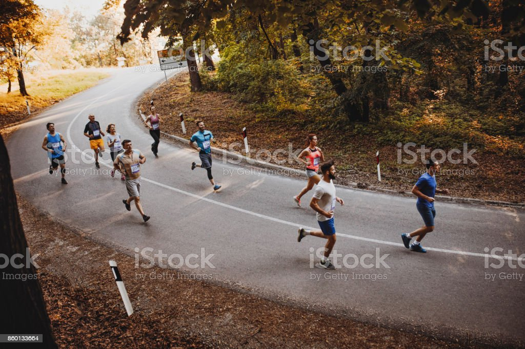 Above view of large group of runners running a marathon on the road. stock photo