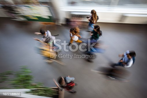 High angle view of large group of students running through the school hallway. Blurred motion.