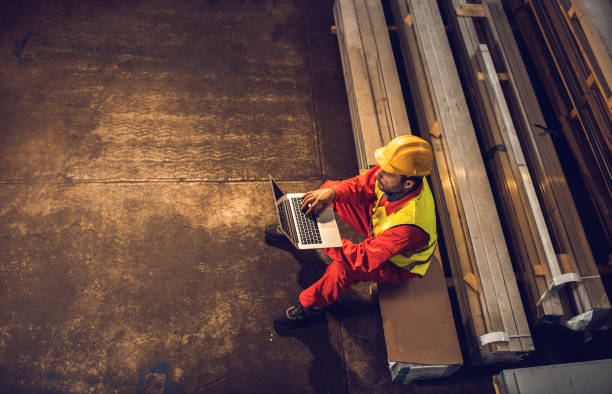 Above view of manual worker using laptop in aluminum mill. stock photo