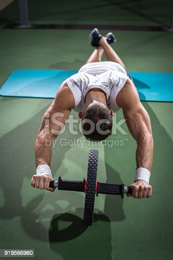 istock Above view of muscular man doing exercises with ab wheel at gym. 919566960