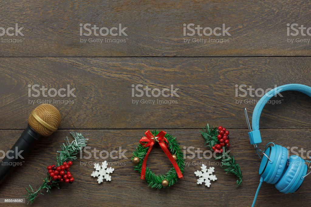 Above view of ornaments & decorations Happy new year and Merry Christmas with music concept.Mix objects composition on the modern rustic brown wooden at home office desk.Free space for creative font. stock photo