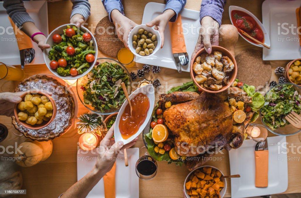 Above view of passing food during Thanksgiving dinner. - Zbiór zdjęć royalty-free (Czynność ruchowa)