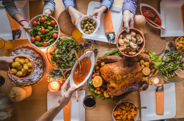 au-dessus de la vue de passer la nourriture pendant le dîner de thanksgiving. - table cuisine photos et images de collection