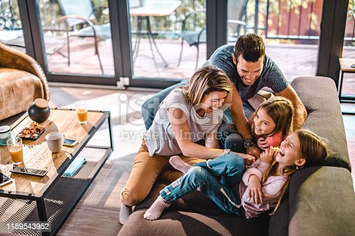 istock Above view of playful parents tickling their daughters at home. 1159543952