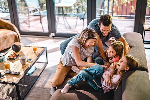 High angle view of cheerful parents having fun while tickling their daughters on sofa in the living room.